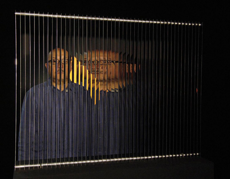 Sebastian Lopez behind an artwork of Julio Le Parc
